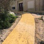 שביל כניסה לבית צהוב דמוי סלע